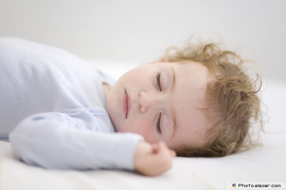 A Young Child Asleep On The Bed