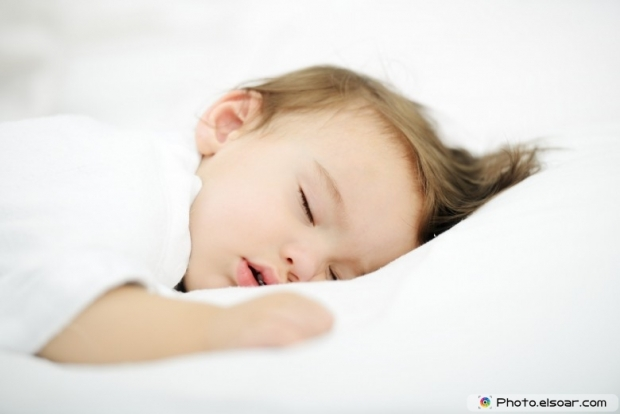 Adorable baby sleeping on white bed
