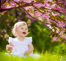 Girl, laughing amid the trees and green grass