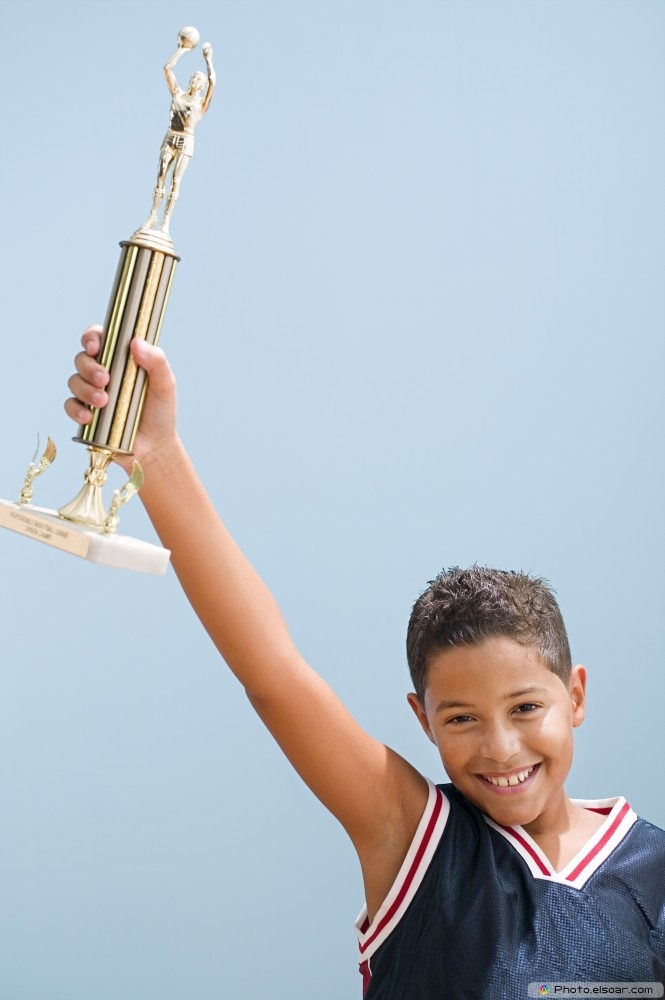 Photo - Boy Holding Up Basketball Trophy