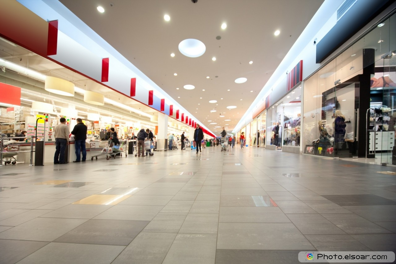 Wide hall in trading center with shops